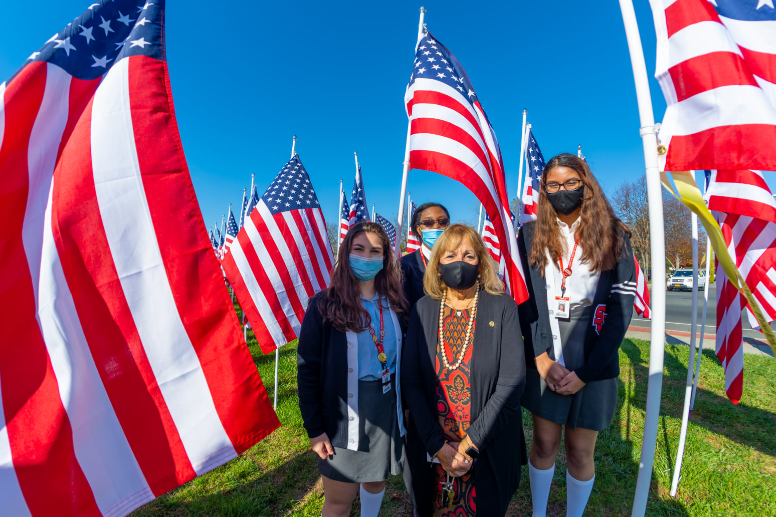 Supervisor with young ladies surrounded by flags