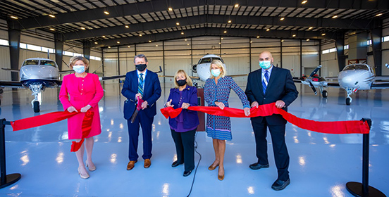 Town officials stand in the new hangar at Islip MacArthur Airport. They are cutting a ribbon to launch the unveiling of the new 32,000 sq facility.