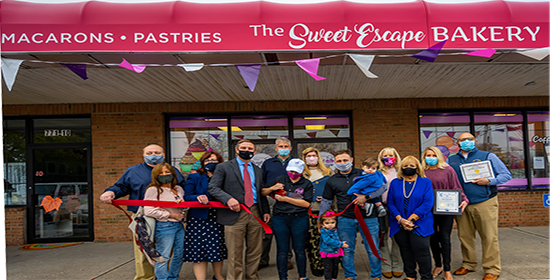 Supervisor Angie Carpenter is joined by the bakery's owner, family members of the owner, bakery staff, Chamber of Commerce members and other elected officials to congratulate the opening of the new Sweet Escapes Bakery in Bayport at the ribbon cutting ceremony.