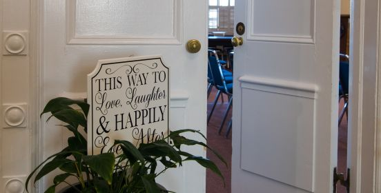 An image of the Town Board room doors cracked slightly open with a sign in the foreground saying, this way to love, laughter, and happily ever after.
