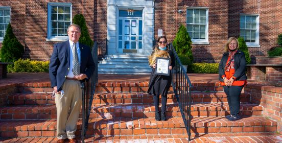 Supervisor Carpenter, Councilman O'Connorr and Isabella Costello pose with recognition award on Town Hall Steps