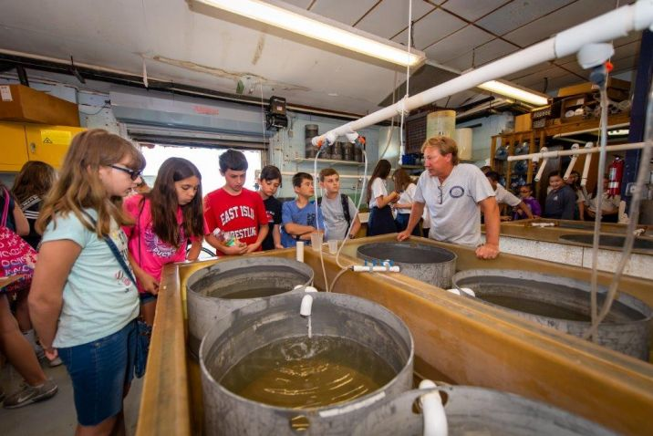 A group of students are shown cultivation tanks inside the facility
